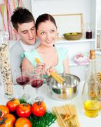 close couple preparing spaghetti in the kitchen and drinkng wine - stock photo