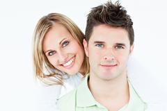 portrait of a young happy couple standing against a white background - stock photo