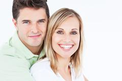 adorable couple smiling at the camera and standing against a white background - stock photo