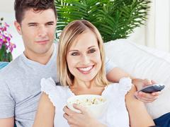 Stock Photo of portrait of an attractive couple with pop-corn and remote relaxing on the sof