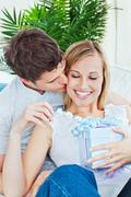 attentive man kissing her girlfriend after giving her a present both lying on - stock photo