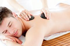 Stock Photo of positive young man enjoying a back massage with hot stone