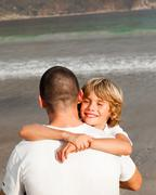 portrait of a cute boy hugging his father - stock photo
