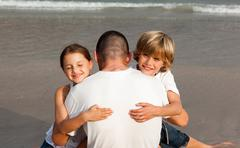 united family on the beach having fun - stock photo