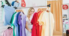 Merry blond woman choosing colorful clothes Stock Photos