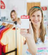 Stock Photo of caucasian blond woman holding a sale paper into the camera