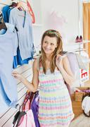 cute young woman choosing clothes in a shop - stock photo