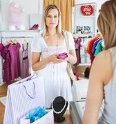serious young woman buying clotheslooking at the camera - stock photo