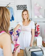 smiling saleswoman giving clothes to a female customer - stock photo