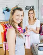 delighted woman taking shopping bag of a saleswoman - stock photo