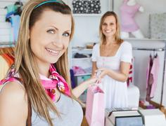 pretty woman taking shopping bag smilig at the camera - stock photo