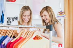 pretty female friends doing shopping choosing shirts - stock photo