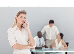 self-assured female talking on the phone with her team - stock photo