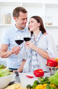 Stock Photo of affectionate couple drinking wine while cooking