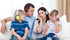 Family listening music with headphones Stock Photos