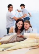 Stock Photo of smiling family doing up their new home