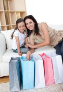 smiling mother and her daughter opening shopping bags - stock photo