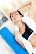 tired hispanic woman sitting on the sofa after working out - stock photo