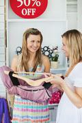 Stock Photo of attractive women choosing clothes together