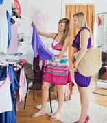 bright women choosing clothes together - stock photo