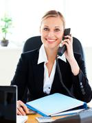 radiant businesswoman talking on phone in her office - stock photo