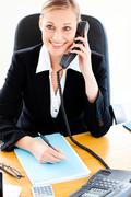 self-assured businesswoman talking on phone and writing in her office - stock photo
