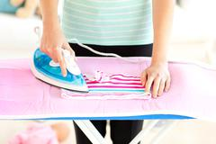 close-up of a caucasian woman ironing her clothes - stock photo