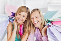 Delighted two women holding shopping bags smiling at the camera Stock Photos