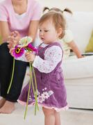 Stock Photo of adorable little girl holding flowers in the living-room