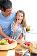 jolly father and his daughter having breakfast - stock photo