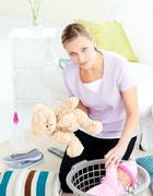depressed young mother putting toy into a basket - stock photo