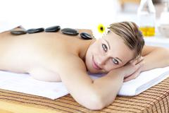 glowing young woman with hot stone on her back smiling at the camera - stock photo