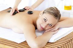 Stock Photo of smiling caucasian woman receiving a massage with hot stone
