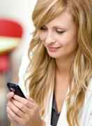 radiant businesswoman sending a text message with her cellphone in her office - stock photo