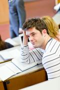 Bored male student during an university lesson Stock Photos