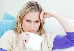 diseased woman lying on a sofa with tissues - stock photo