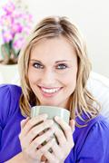 joyful young woman holding a cup of coffee on a sofa - stock photo