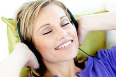 charming caucasian woman listening to music with headphones lying on a sofa - stock photo