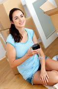 Young woman drinking wine after unpacking cardboards Stock Photos