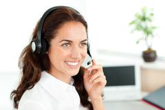 smiling woman with headset working in a call center - stock photo