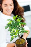 glowing businesswoman holding a plant smiling at the camera - stock photo