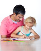 Stock Photo of beautiful daughter painting with her father