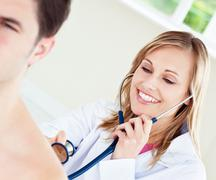 Stock Photo of smiling doctor is examinating her patient