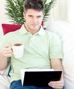 Joyful young man holding a cup of coffee and a laptop Stock Photos