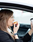 Attractive businesswoman eating and holding a drinking cup while driving Stock Photos