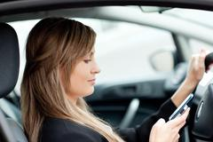 Stock Photo of beautiful businesswoman sending a text while driving