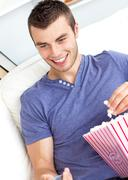 Stock Photo of positive caucasian man holding a remote and eating popcorn in the living-room