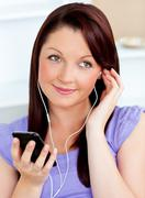 Attractive woman using her cellphone to listen to music with earphones Stock Photos