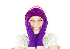 positive woman with a colorful hat and a pullover smiling at the camera - stock photo