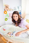 attentive young mother taking care of her adorable baby - stock photo